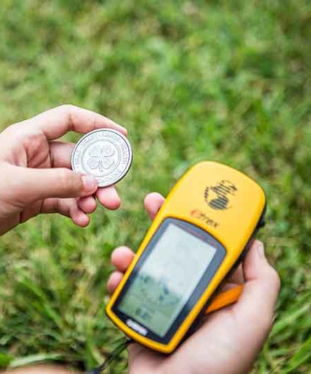 Child holding a coin with a 4-H logo and a GPS navigator